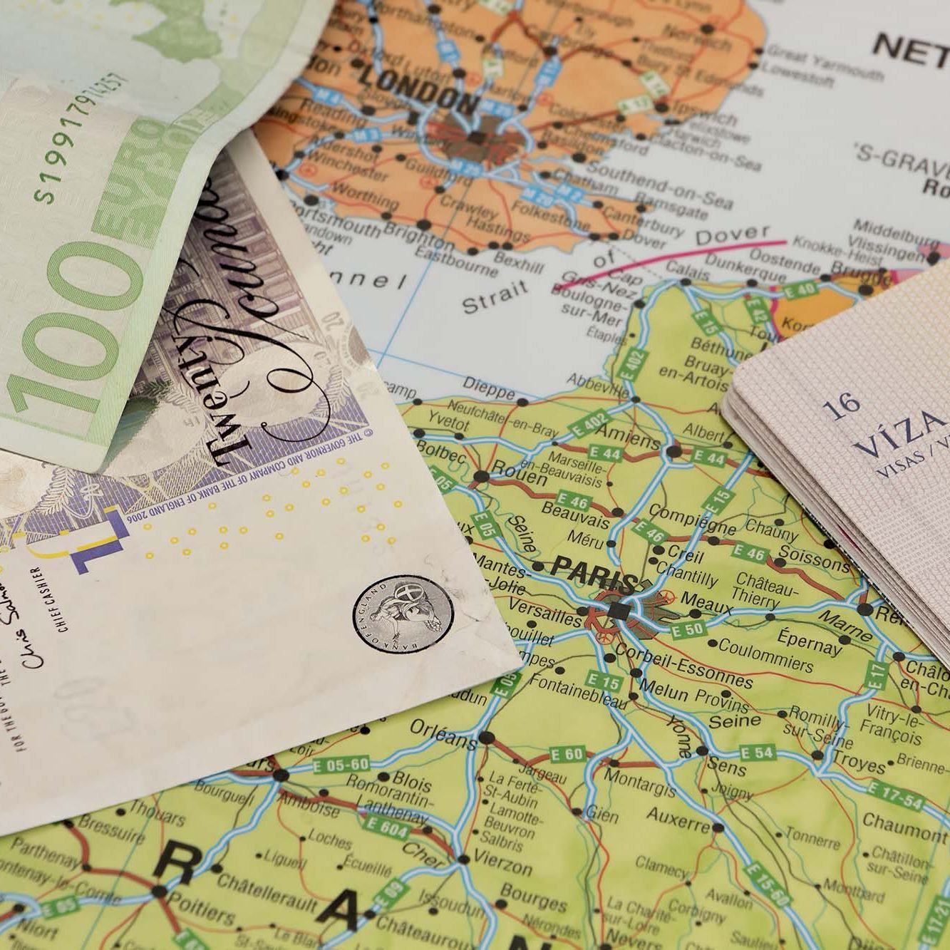 Passport and money sitting on a map showing Paris & London